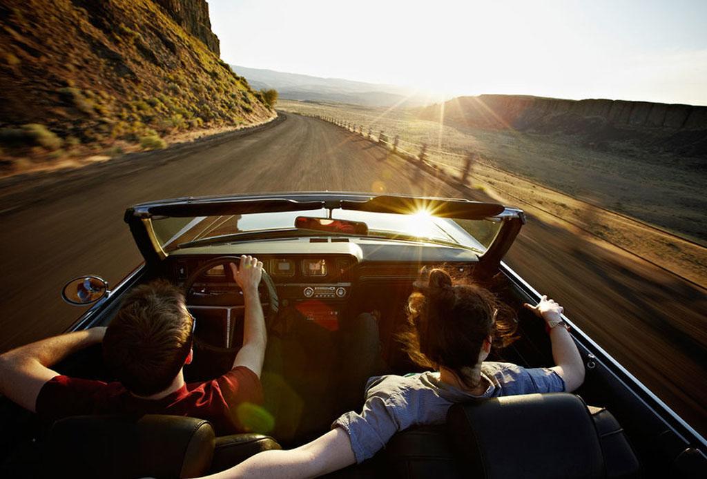 pareja en carretera con el atardecer